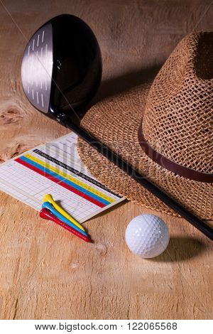 Siesta - straw hat and golf driver on a wooden table