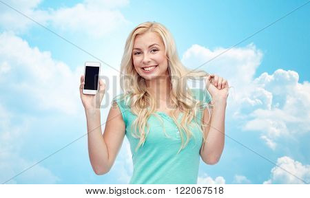 emotions, expressions, technology and people concept - smiling young woman or teenage girl showing blank smartphone screen over blue sky and clouds background