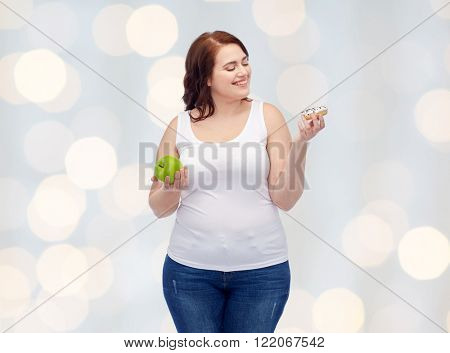 healthy eating, junk food, diet and choice people concept - smiling plus size woman choosing between apple and donut over holidays lights background