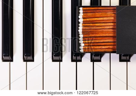Detail of piano keyboard and luxury matchbox