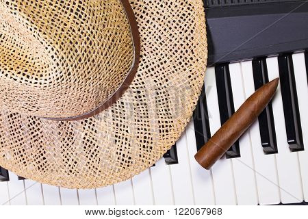 Detail of piano keyboard straw hat and luxury cigar