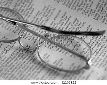 Reading glasses resting on newspaper