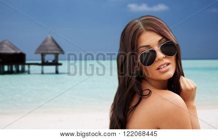 summer vacation, tourism, travel, holidays and people concept -face of young woman with sunglasses over bungalow on beach background