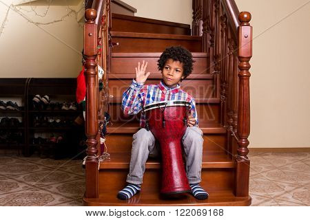 Boy with drum on stairs. Afro boy's Christmas drum performance. H
