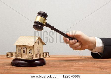 Auction, Real Estate concept. Hand with judge gavel and house model.