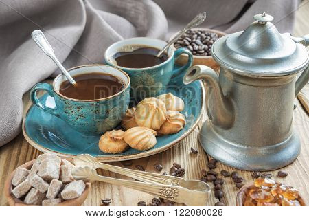 Two blue cups of black coffee biscuits and coffee pot surrounded by linen cloth sugar pieces and coffee beans on old wooden table