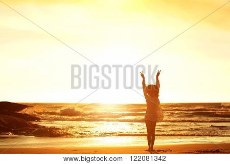 Woman Standing At Beach With Arms Raised And Peace Sign