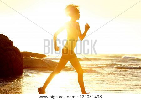 Female Runner By The Sea During Sunset