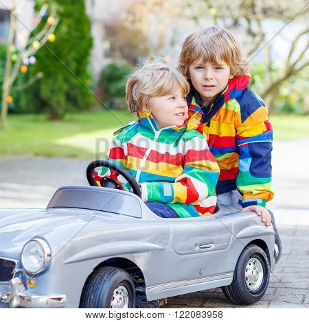 Two little twins kid boys playing with big old vintage toy car in spring or autumn garden, outdoors. Active leisure with kids outdoors  on warm spring or autumn day.