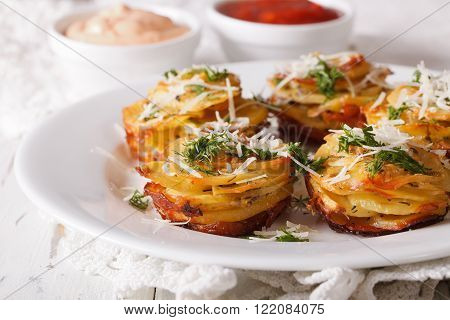 Baked Sliced Potatoes With Parmesan Close-up On A Plate. Horizontal