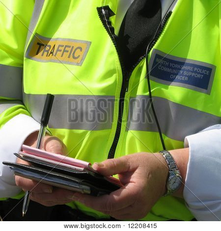 Close-up of community support police officer issuing parking tickets