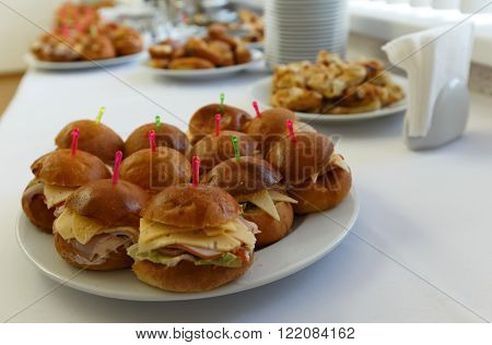 Selective focus photo catering banquet table with baked food snacks sandwiches cakes and plates self serve open buffet dinner horizontal view