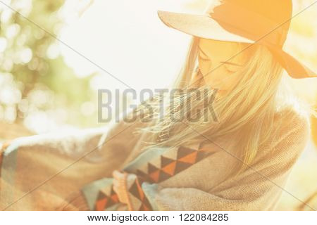 Attractive fashionable girl in a hat and poncho walking at sunny day outdoor