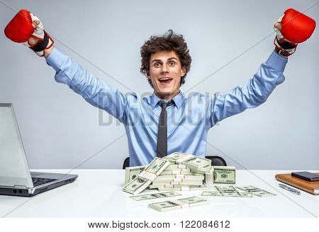 Victory in business. Winner businessman in boxing gloves / Entrepreneur is satisfied with his profit income earnings gain benefit. Businessman at the workplace on grey background