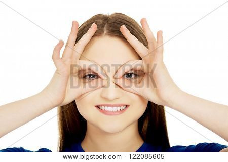 Woman showing perfect sign on eyes.