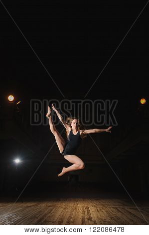 Photo of young brunette dancer girl in split jump on stage in theater with spotlight. ballet dancer in black clothes. barefoot dancer.
