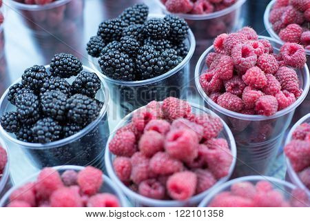 Raspberries and black berry on the table. Blackberries and raspberries in bowls top view close-up. Selective focus.