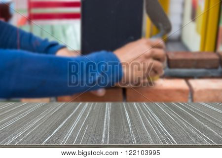 the worker is using the trowel for masoning the brick (blur background and wooden table for displaying your product)