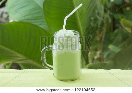 Matcha Green Tea smoothie for refreshment on garden background