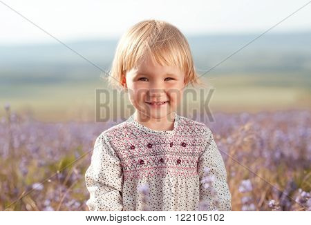 Laughing cute kid girl 2-3 year old wearing stylish dress in lavender meadow. Looking at camera. Childhood.