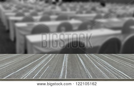 empty table and chair with fabric covering in convention hall (blur background and wooden table for displaying your product)