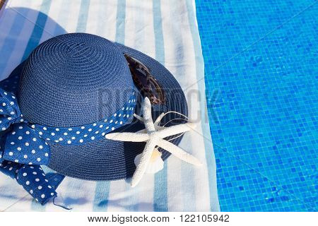 towel and summer hat with seashells near water of pool