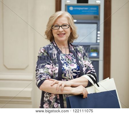 Mature blonde woman with shopping bags on the background of the ATM