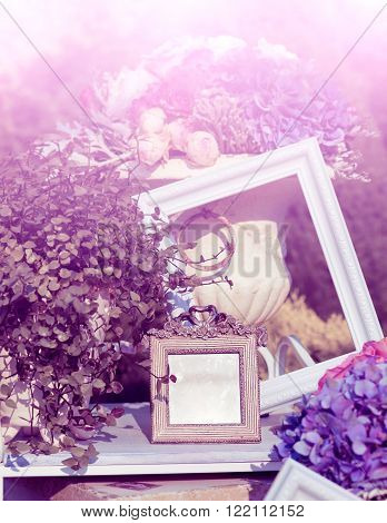 Photoframes and vase with flowers in the garden