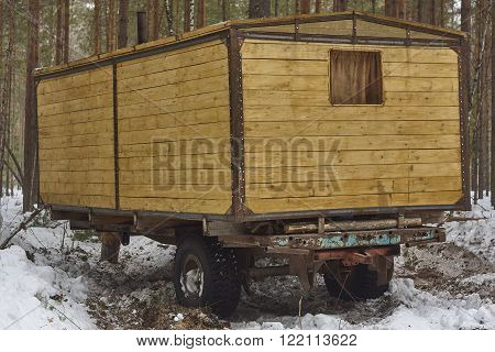handmade house on wheels. Pine tree forest window snow wood board iron nail chimney yellow brown green Siberia