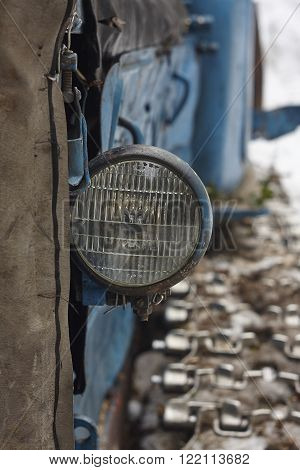 old spotlamp on tractor. old spotlamp on tractor. iron rust wire blue hanger texture close up track
