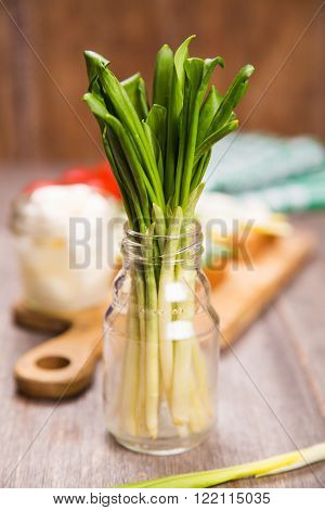 fresh green ramson in glass container on wooden background