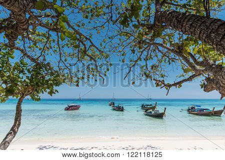 Sea Beach with Long tail boat and Leaves of tree background at Thailand