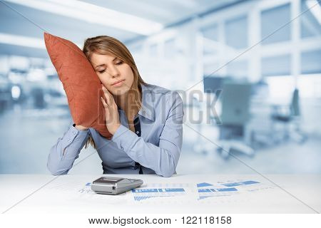 Woman having a rest (sleep relax) in work. Burnout tired worker concept. Weary woman with pillow graphs sheets and calculator office in background.