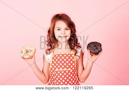 Smiling baby girl 4-5 year old holding two donuts in hands over pink. Looking at camera. Childhood. Tasty cakes. Cooking.