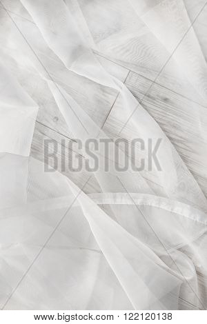 White draped transparent tulle on wooden floor as a background
