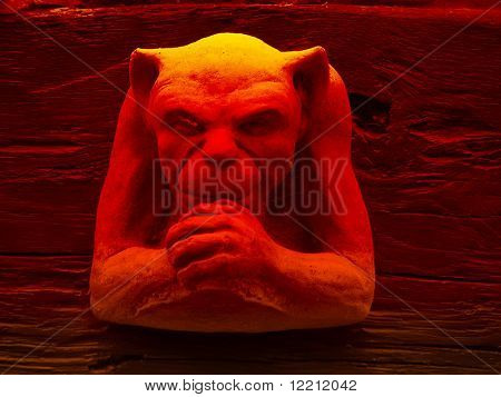 Carved gargoyle sculpture with red lighting effect.