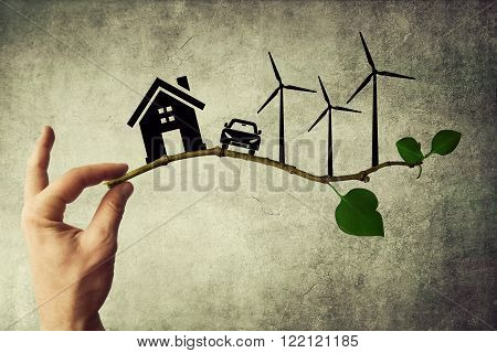 Human hand holding a tree branch. Environmental green energy concept. Silhouette of house car and wind turbine