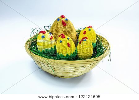 A brood of crochet chickens in a wicker basket.