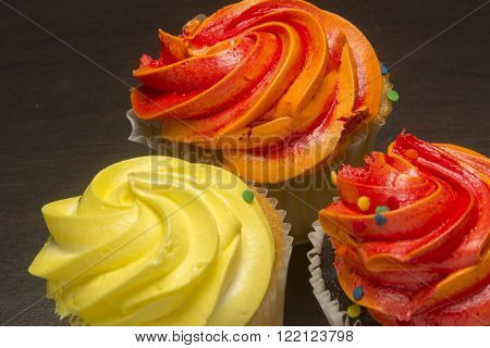 Orange and yellow cupcakes with sugary frosting
