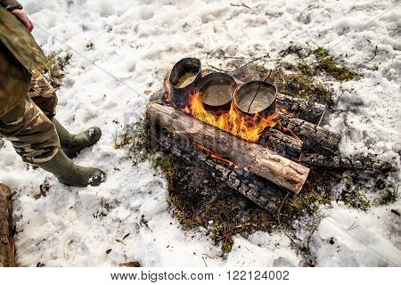 Cooking in a winter hike in the cauldron hanging over the fire in the snow-covered pine forest while camping on a sunny day man stands near