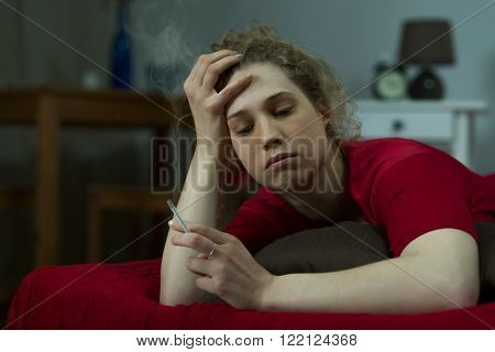 Image of young lonely woman smoking cigarette in bed