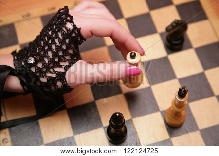 Female hand in black openwork knitted gloves on a background of a chessboard