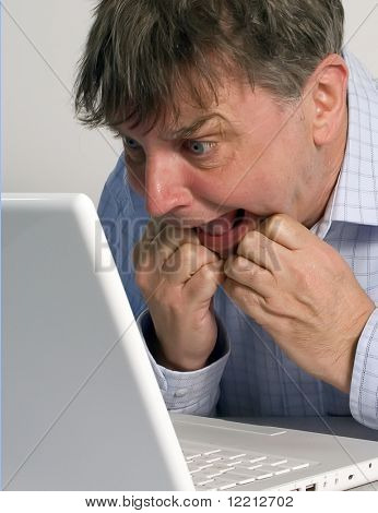 Middle aged man looks at his laptop in disbelief