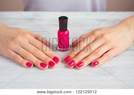Female hands with pink manicure and a bottle of lacquer on a wooden table