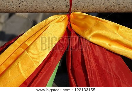 Yellow green and red ribbons tied to a stone railing within Nanxiang Ancient Town for the spring festival celebrations in Shanghai China.