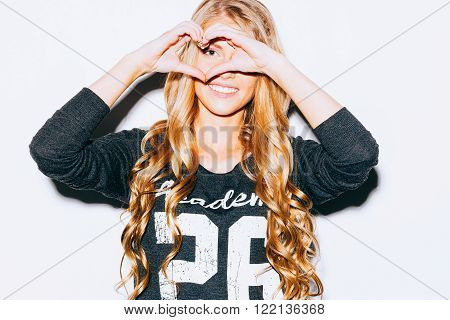 Love. Closeup portrait smiling happy young woman with long blon hair, making heart sign, symbol with hands white wall background. Positive human emotion expression feeling life perception attitude body language. Indoor. Warm color. Hipster.