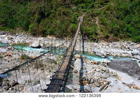Rope hanging suspension bridge under the river in mountains, Nepal