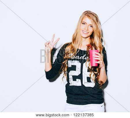 Happy Young Woman Showing Victory Sign and holding a pink glass with straw in hand On White Background. Indoor. Warm color. Hipster.