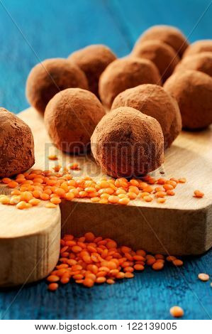 Homemade vegetarian lentil sweets in cocoa powder on wooden board with orange lentils vertical