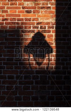 shadow of a street lamp on an old brick wall unusual dramatic background texture with copy space selected focus